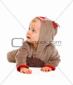 Baby in costume of Santa Claus's reindeer looking in corner