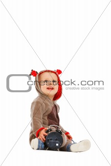 Baby in costume of Santa Claus's reindeer with alarm clock looking up