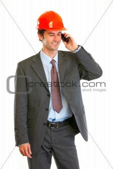 Smiling architect in helmet speaking mobile