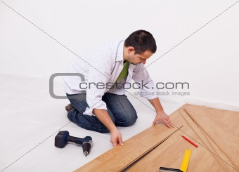 Casual man or worker installing flooring