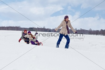 Children sleigh riding - their mother