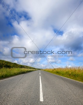 An empty English countryside road and a big sky in Cornwall.