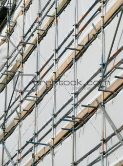 Close up building covered by scaffolding and white tarpaulin.