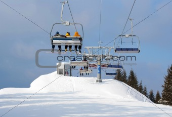 Skiers in chairlift arriving to top of mountain