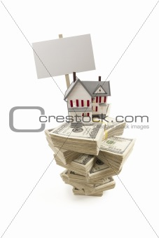 Small House on Stacks of Hundred Dollar Bills and Blank Sign Isolated on a White Background.