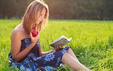 Beautiful woman sitting in the grass is reading book with apple in hand