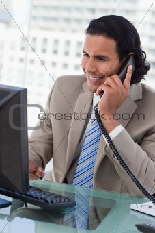 Portrait of a businessman working with a monitor while being on the phone