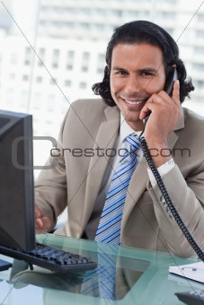 Portrait of a businessman working with a monitor while being on the telephone