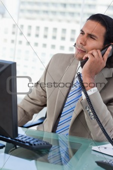 Portrait of a handsome businessman working with a monitor while being on the phone