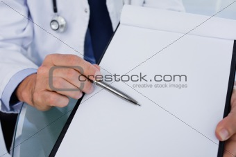 Close up of a male doctor showing a blank document