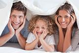 Family posing under a duvet