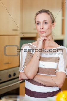 Woman in thoughts standing in kitchen