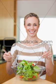 Smiling woman stirring salad