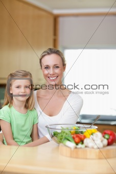 Smiling mother and daughter in the kitchen