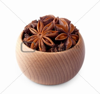 Wooden bowl full of anise stars isolated on white
