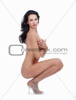 beautiful nude woman with dark hair looking at camera - isolated on white