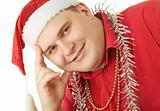 Smiling young man in a red shirt, hat Santa Claus and tinsel in
