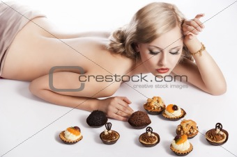 blond sexy girl eating pastry, she has right hand near her head