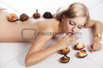 blond sexy girl eating pastry, she has one finger in mouth