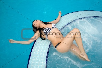 Beautiful sexy brunette swimming in a pool