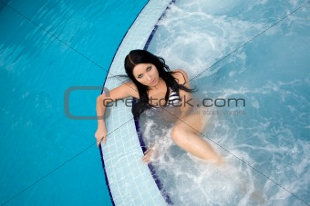 Attractive sexy brunette swimming in a pool