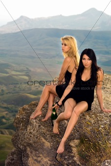 Two young women with a champagne bottle sit on a rock