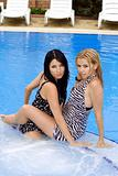 Portrait of the two beautiful young girlfriends in pool
