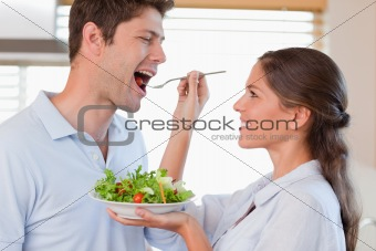 Accomplice couple tasting a salad