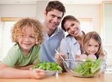 Smiling family preparing a salad together