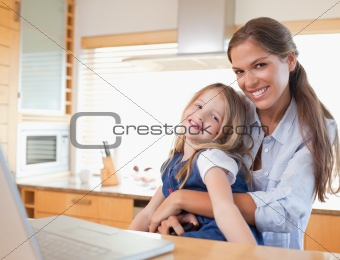 Happy mother and her daughter using a laptop