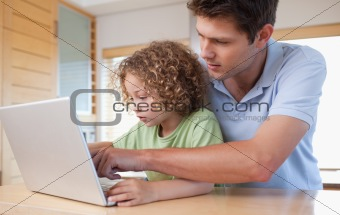 Boy and his father using a laptop