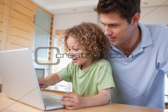 Boy and his father using a notebook