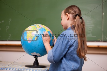 Focused schoolgirl looking at a globe