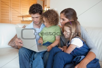 Focused family using a laptop