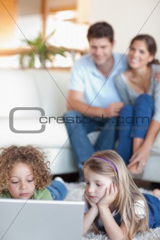 Portrait of cute children using a laptop while their parents are watching