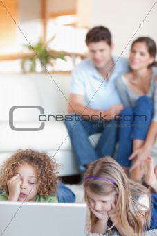 Portrait of children using a laptop while their parents are watching
