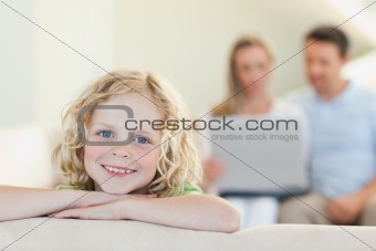 Smiling boy with parents in the background