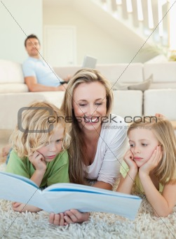 Mother reading magazine with her children on the floor