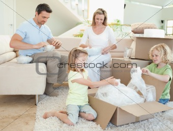 Family unpacking cardboard box
