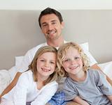 Father sitting on bed with his children