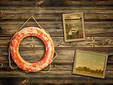 lifebuoy and old travel photos at wooden background