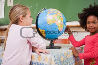 Cute schoolgirls looking at a globe