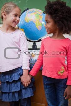 Portrait of smiling schoolgirls holding hands