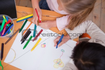 Above view of little schoolgirls drawing
