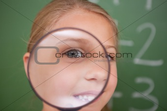 Close up of a schoolgirl looking through a magnifying glass