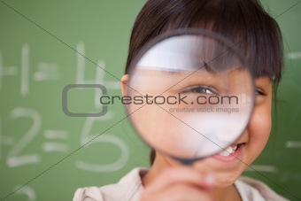Close up of a cute schoolgirl looking through a magnifying glass