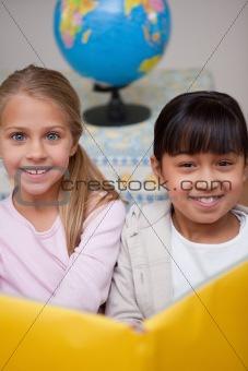 Portrait of happy schoolgirls reading