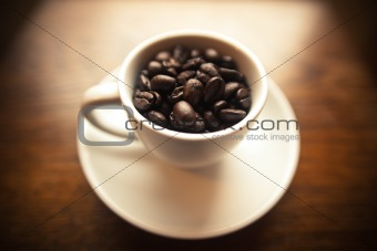 Coffee beans in white coffee mug
