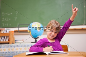 Schoolgirl raising her hand to ask a question
