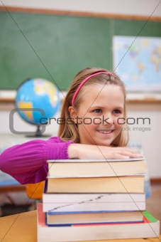 Portrait of schoolgirl posing with a stack of books